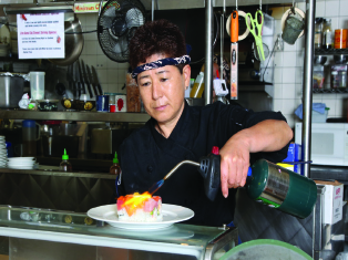 Chef Miki prepares a Laguna Canyon roll with a blowtorch.
