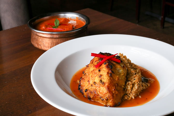 Chicken tikka masala (back) and tandoori sea bass tempt diners with flavorful sauces.
